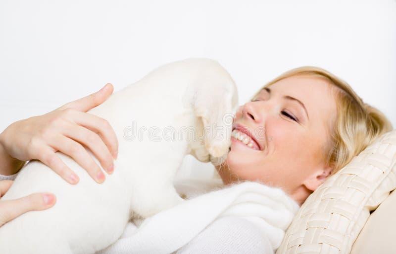 Cachorrinho de Labrador que encontra-se na mulher fotos de stock royalty free
