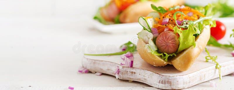 Cachorro quente com pepino, cenoura, tomate e alface no fundo de madeira imagem de stock royalty free