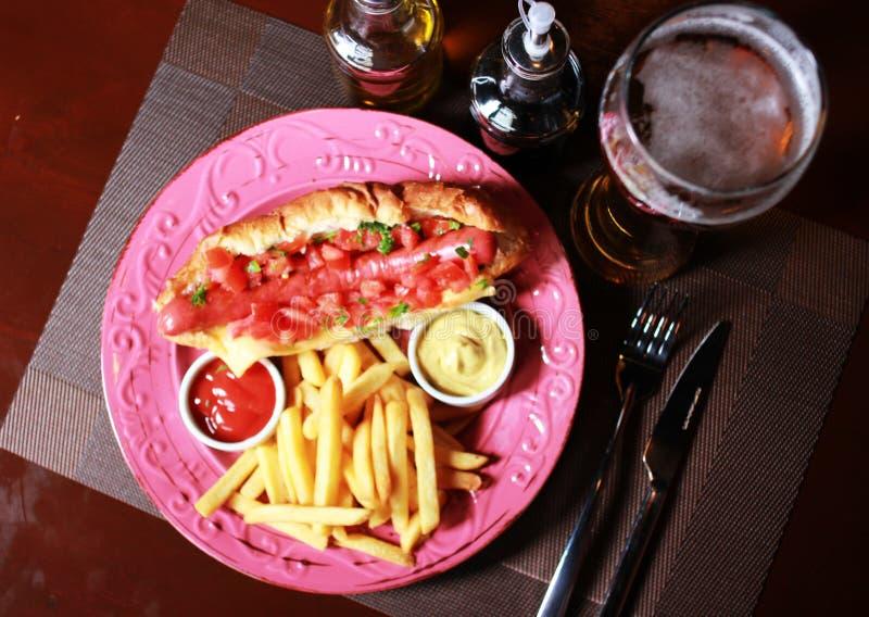Cachorro quente com salsa, cerveja fria e batatas fritas fotografia de stock royalty free