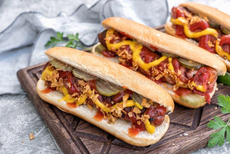 Cachorro quente com a salsicha envolvida bacon, a ketchup, mostarda amarela, a cebola fritada e as salmouras imagens de stock