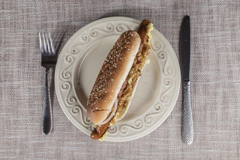 Cachorro quente saboroso fresco com cebolas fritadas e alface fresca com mostarda em uma placa da porcelana com forquilha e faca fotografia de stock