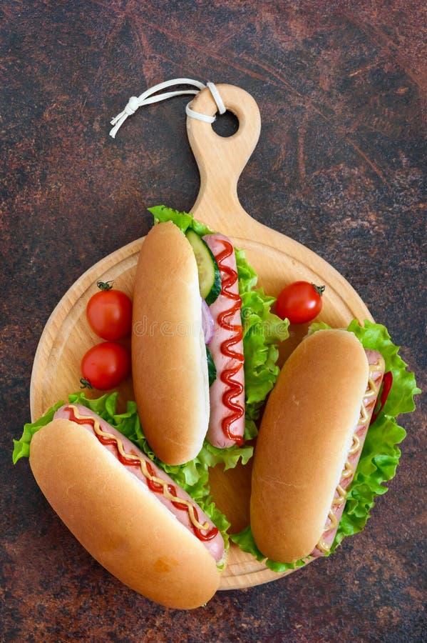 Cachorros quentes deliciosos com grade da salsicha, ketchup, mostarda, alface, tomates em uma bandeja de madeira imagem de stock