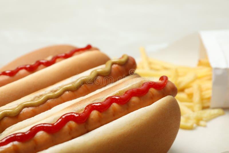Cachorros quentes saborosos com mostarda e ketchup na tabela fotografia de stock royalty free
