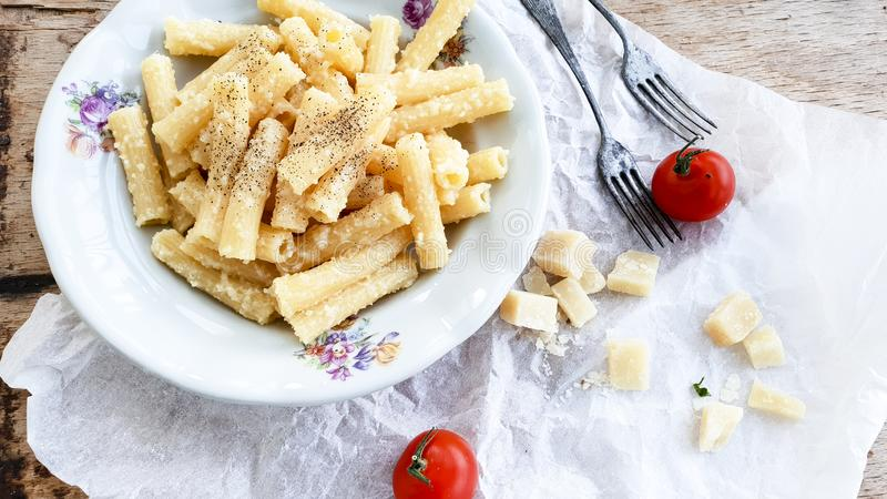 Cacio ε ζυμαρικών rigati Sedani pepe με τις ντομάτες κερασιών και το τυρί παρμεζάνας στοκ φωτογραφία