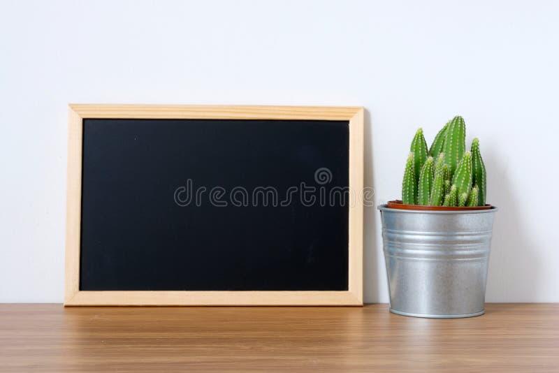 Cacto e quadro vazio do vintage na tabela de madeira e nos vagabundos brancos imagem de stock