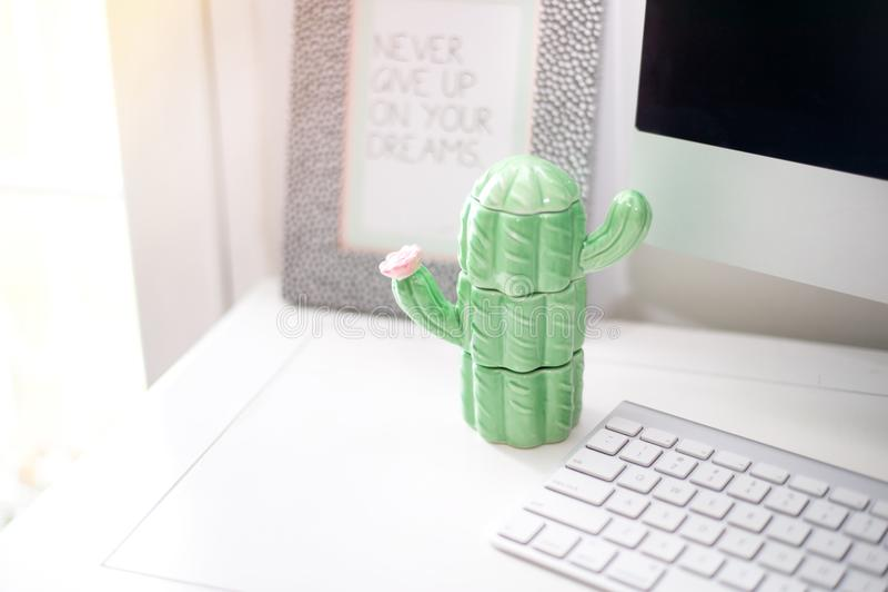 Cactus de la porcelana en una tabla de trabajo cerca de la mesa del ordenador imagen de archivo