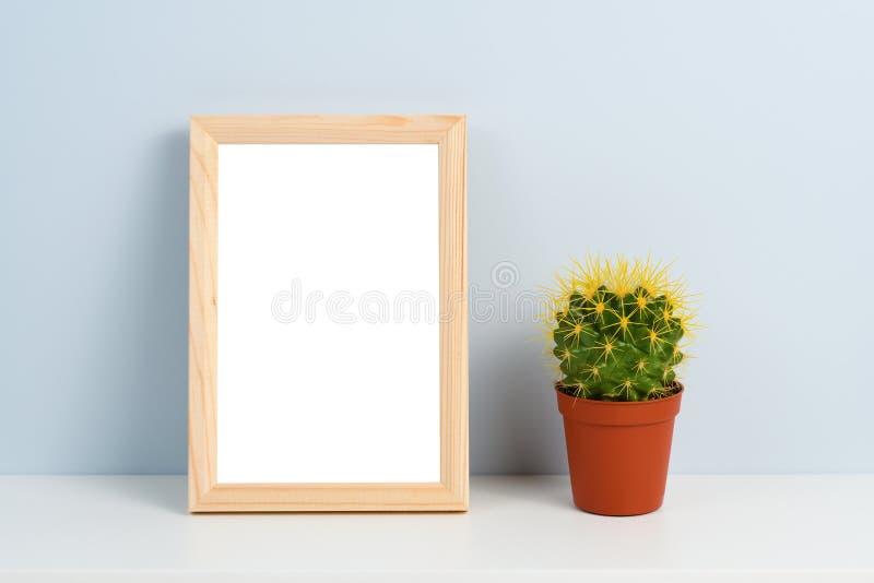 Cactus en pote y marco de madera de la foto fotos de archivo
