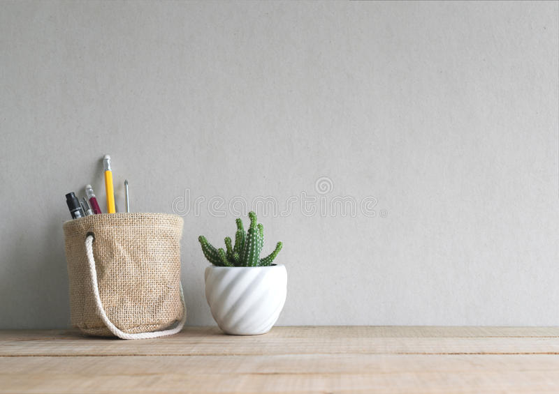 Cactus flower with pen and pencil in holder basket on wood table.  royalty free stock photos