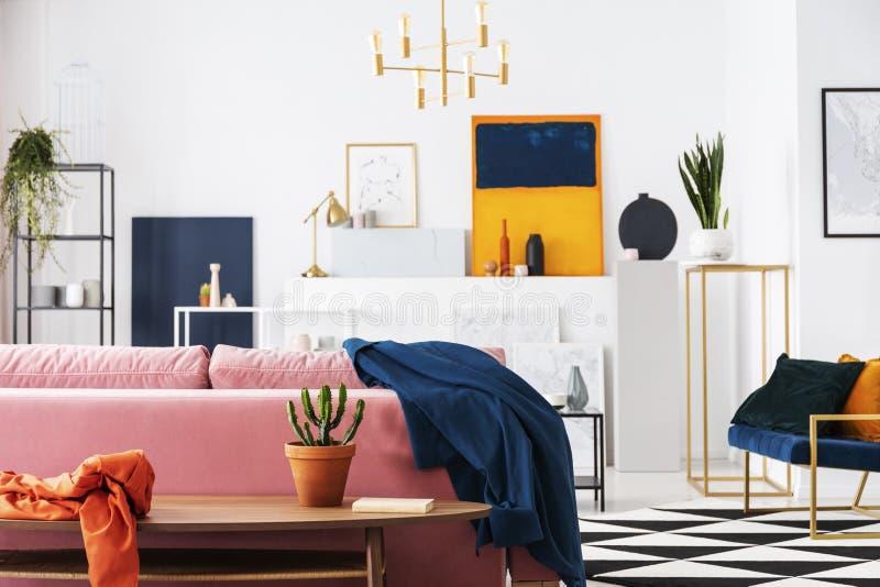 Cactus in pot op de houten lijst in moderne woonkamerflat van kunstcollector, partij van schilderijen op de muur stock fotografie