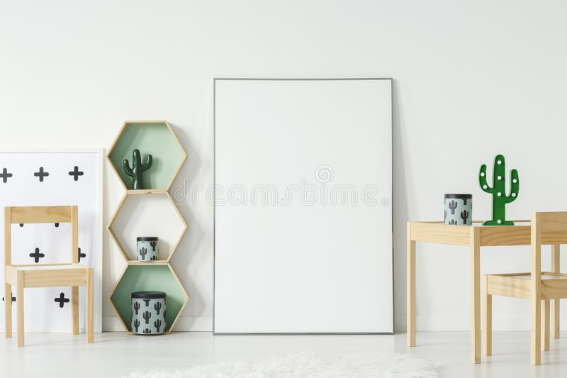Cactus on wooden table next to white empty poster with mockup in royalty free stock image