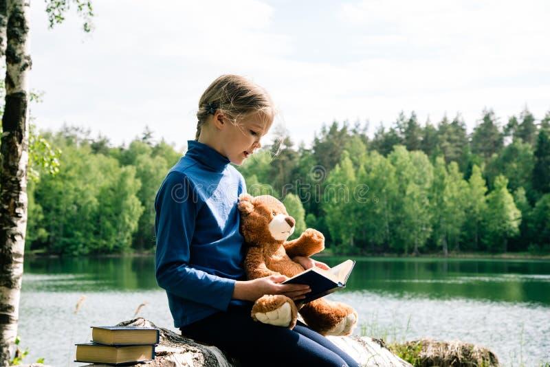 Cada amor Teddy Bear del niño como sus mejores amigos que abrazan y que se ligan para ir a merendar en el campo y a leer el libro fotos de archivo