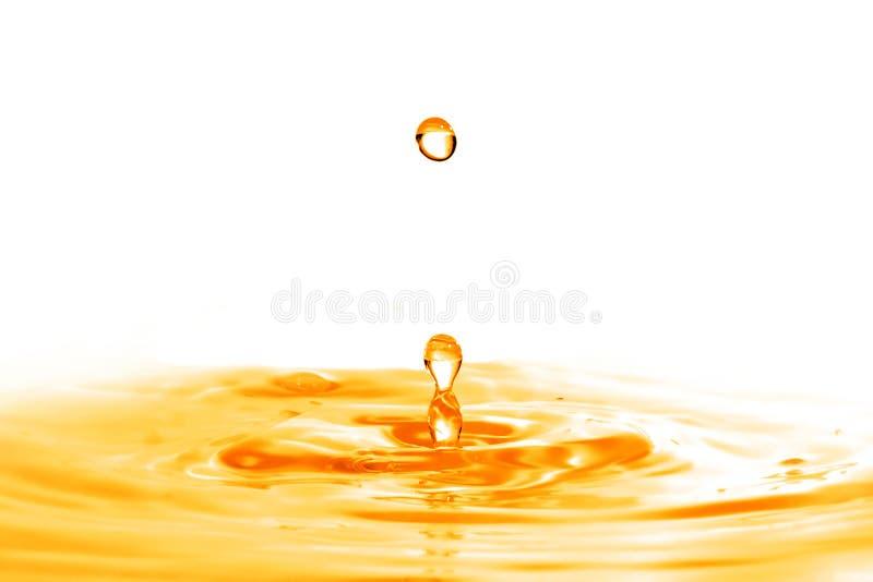 Cada la caduta nell'acqua arancio con spruzzata isolata su bianco immagine stock libera da diritti