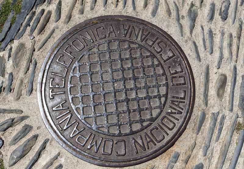 Cast iron manhole cover or gully cover on a street. Close up a manhole cover on road of Cadaques, Spain. stock image