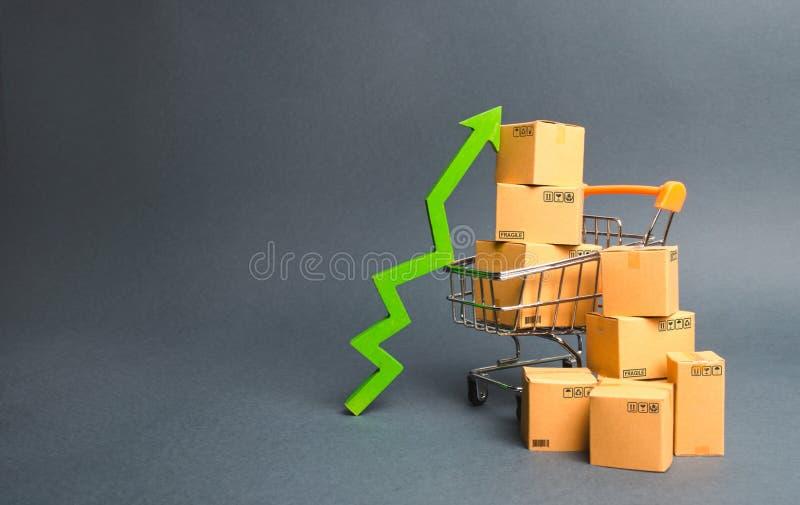 Caddie avec des boîtes en carton et un vert vers le haut de flèche Augmentez le pas des ventes et la production des marchandises images stock