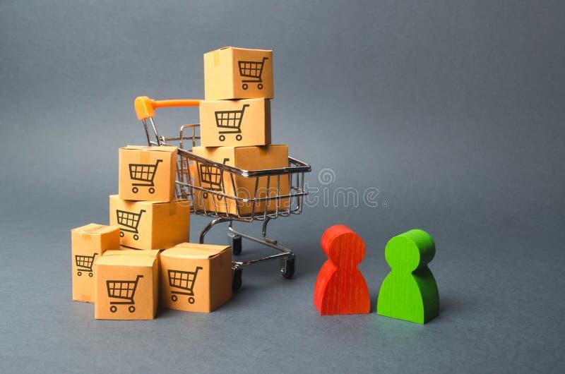 Caddie avec des boîtes en carton avec un modèle des chariots marchands un acheteur et un vendeur, fabricant et détaillant Busines photos libres de droits