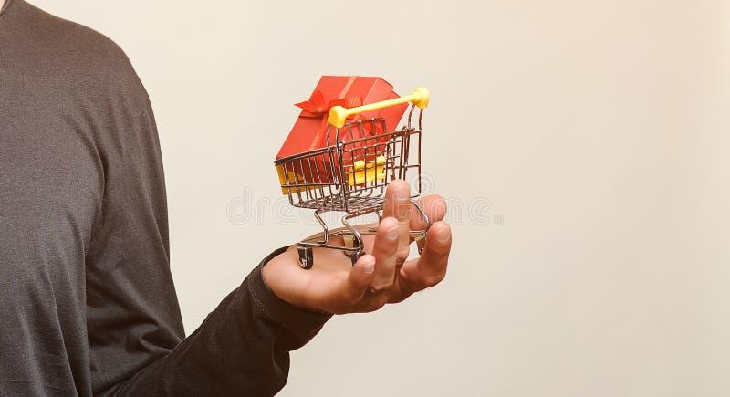 Caddie avec le cadeau dans des mains masculines d'isolement Achats, remise, concept de vente Boîte-cadeau rouge dans le caddie No photo libre de droits