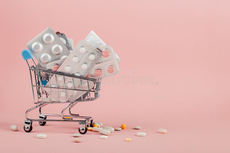 Caddie charg? avec des pilules sur un fond rose Le concept de la m?decine et la vente des drogues Copiez l'espace photographie stock libre de droits