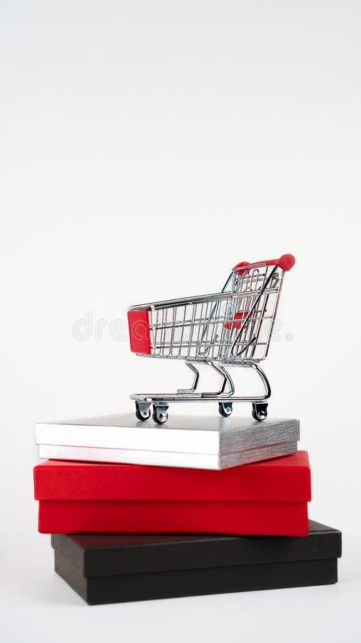 Caddie ou chariot à boutique de supermarché sur des boîte-cadeau sur le fond blanc, l'espace de copie Style de minimalisme Vendre photo stock