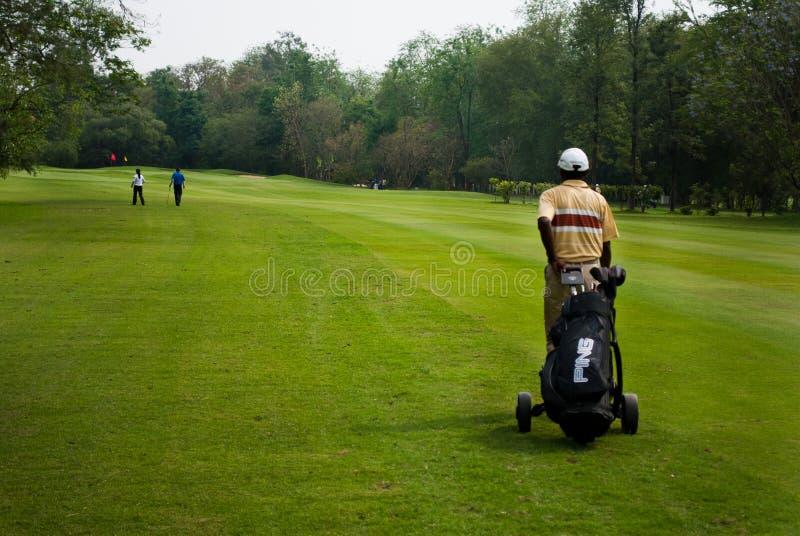 Caddie przewożenia golfisty klub fotografia stock