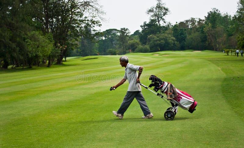 Caddie przewożenia golfisty klub fotografia royalty free