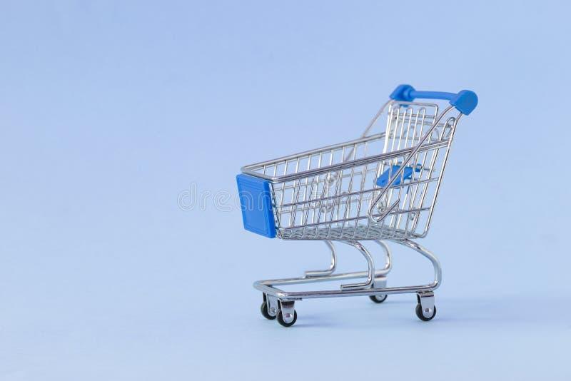 Caddie vide sur le fond coloré Plan rapproché de chariot de achat dessus avec un certain espace de copie Concept du consommateur photo stock