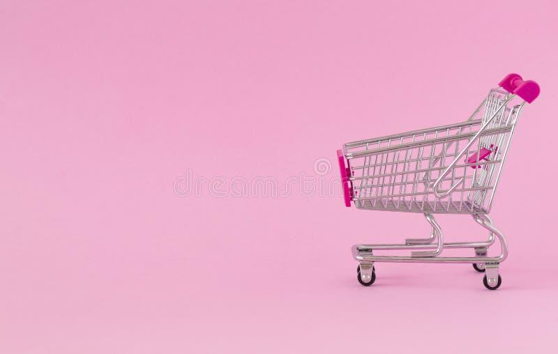 Caddie vide sur le fond coloré Plan rapproché de chariot de achat dessus avec un certain espace de copie Concept du consommateur photos stock