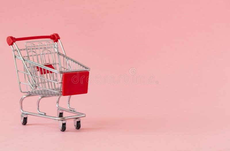Caddie vide sur le fond coloré Plan rapproché de chariot de achat dessus avec un certain espace de copie Concept du consommateur images stock