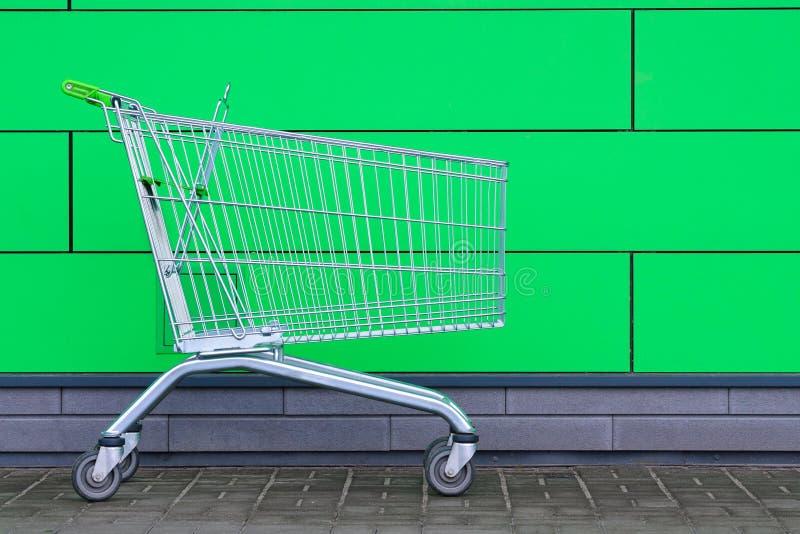 Caddie vide sur le fond vert Le chariot pour des achats, fin  Ventes, remises Achats photographie stock