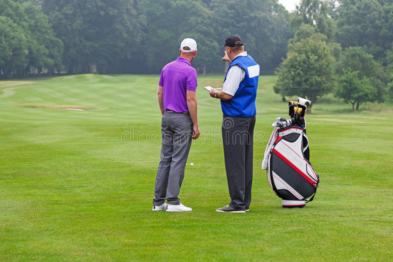 Caddy pointing out a hazard to golfer. Caddy pointing out a hazard to the golfer on a par 4 fairway stock photos