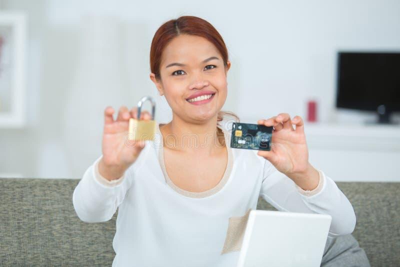 Cadeado da exibição da mulher e cartão de crédito felizes foto de stock royalty free