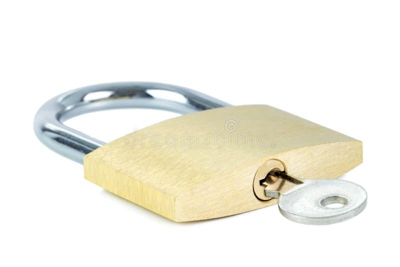 Cadeado fechado com uma chave no buraco da fechadura imagens de stock