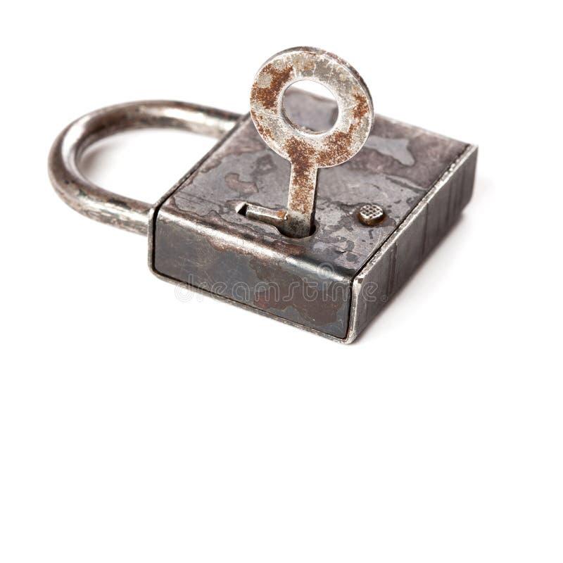 Cadeado fechado do ferro do projeto do vintage chave no furo imagem de stock