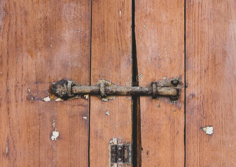 Cadeado fechado velho oxidado no fundo de madeira do marrom da prancha da porta da porta imagem de stock