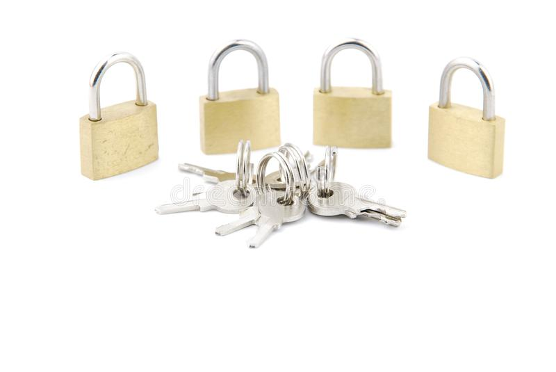 Cadeado fechados dourados com chaves no branco fotografia de stock royalty free