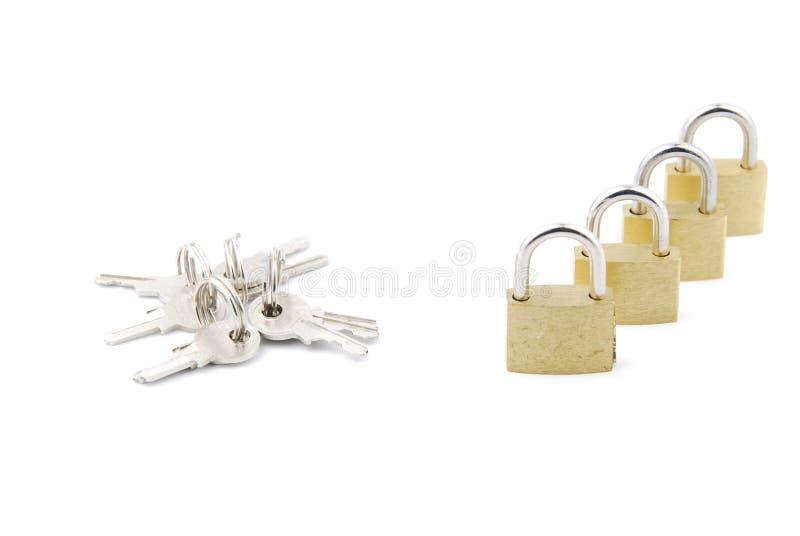 Cadeado fechados dourados com chaves no branco imagem de stock