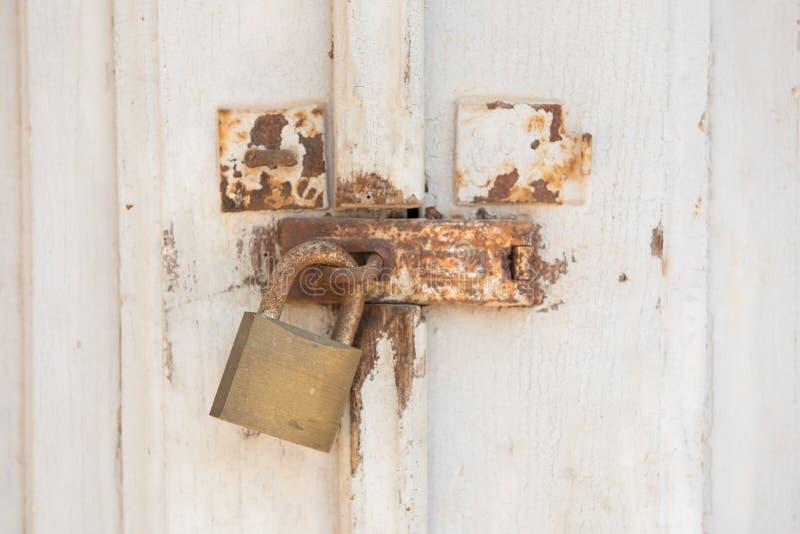 Cadeado velho e oxidado do metal nas portas brancas Porta fechado com fechamento fotos de stock royalty free