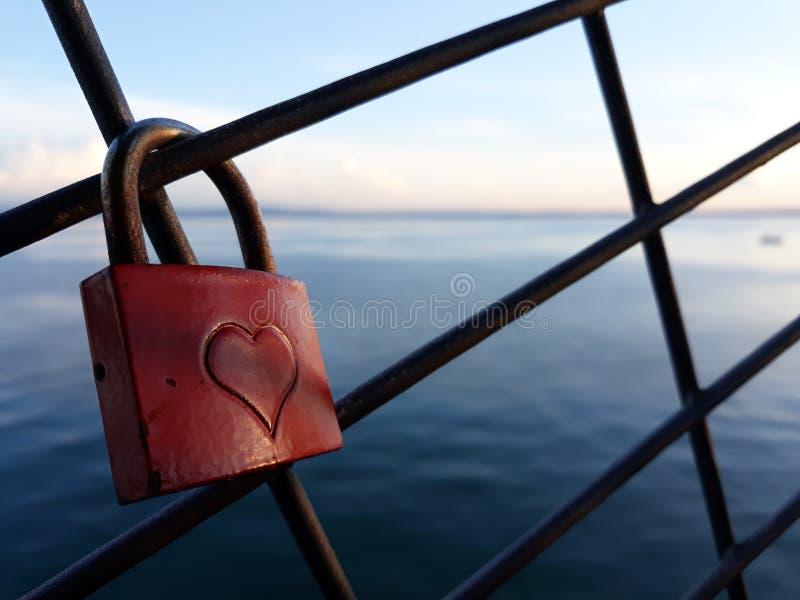 Cadeado vermelho velho e atrás do lago grande imagens de stock