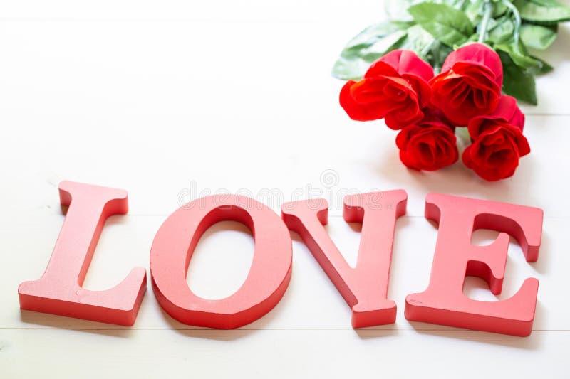 Cadeau actuel avec amour rose rouge de fleur et de mot sur la table en bois, le 14 février avec romantique image libre de droits