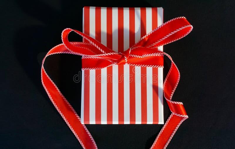 Cadeau brillamment enveloppé sur le fond noir photographie stock