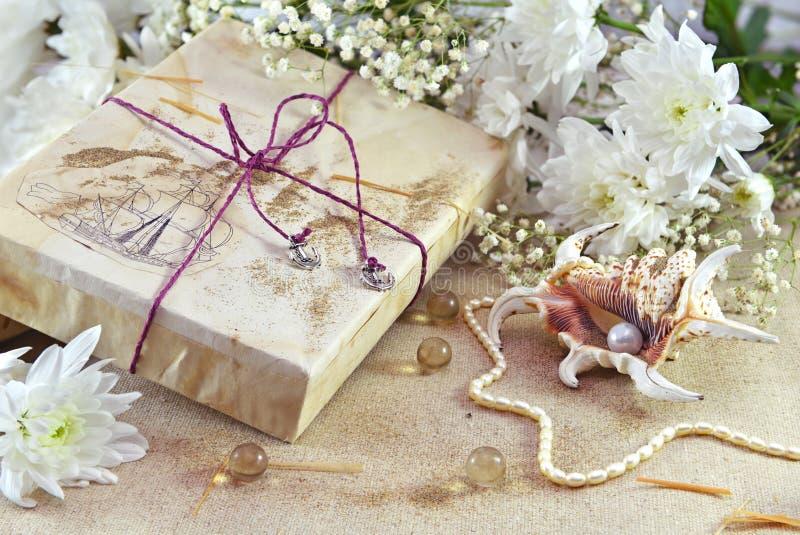 Cadeau décoré avec les fleurs et la coquille de perle photographie stock