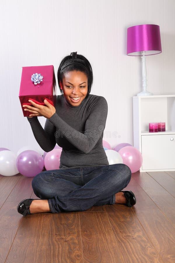 Cadeau d'anniversaire de mystère pour la jeune fille heureuse à la maison images libres de droits