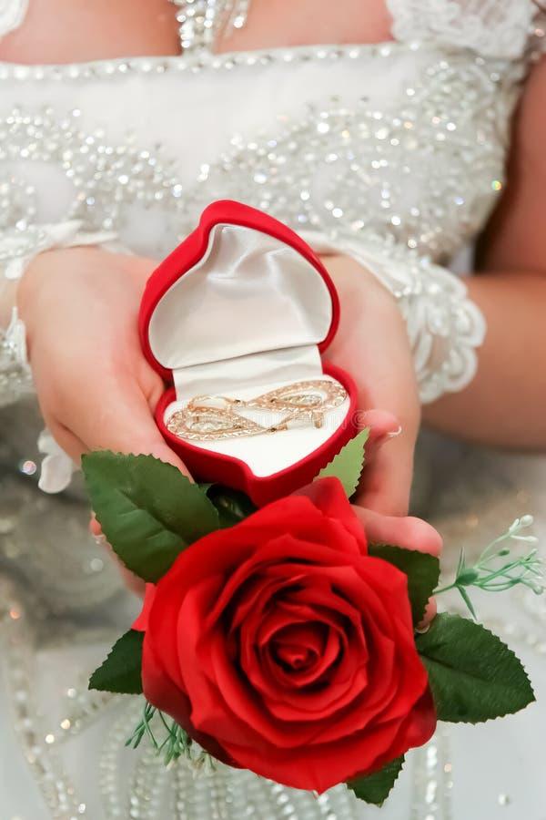 Cadeau d'or dans les mains de la jeune mariée photographie stock libre de droits
