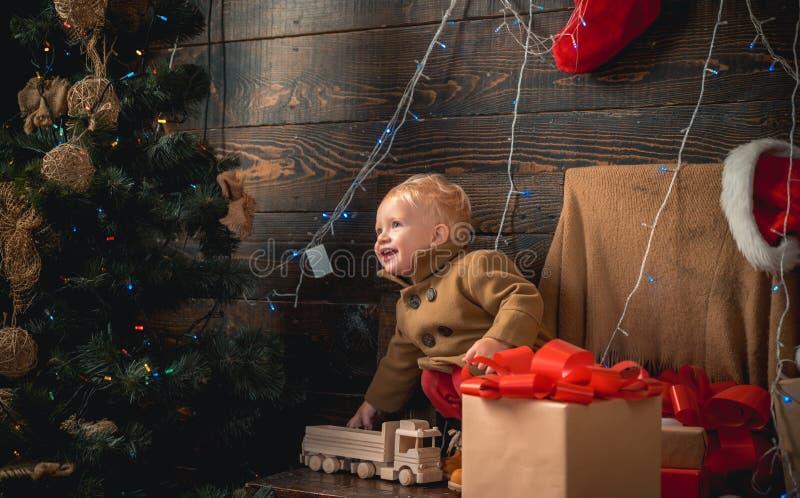 Cadeau d'enfants Carte de Noël Portrait d'enfant heureux regardant la boule décorative de jouet par l'arbre de Noël Noël de Noël photo stock