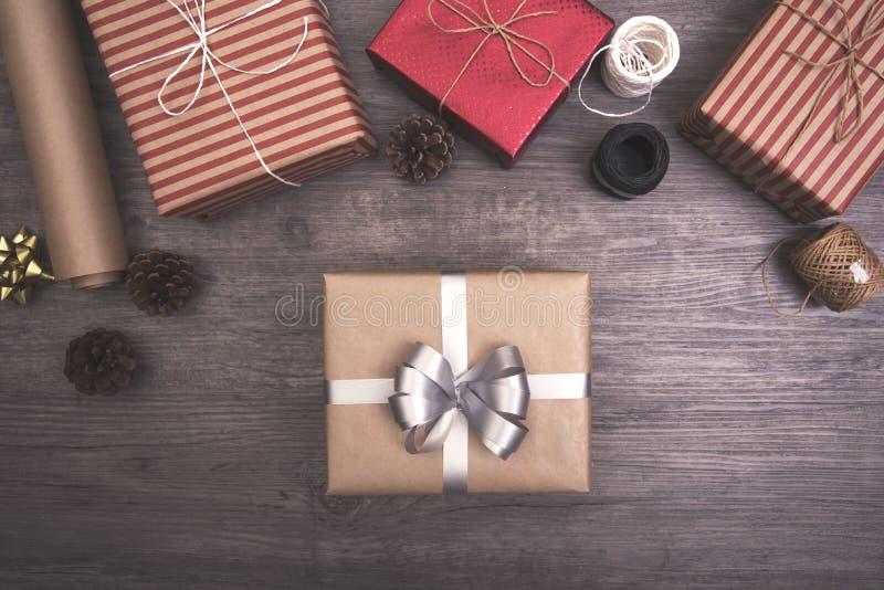 Cadeau de cadeaux de Noël rouge et rustique décoré étendu sur le fond en bois de table image stock