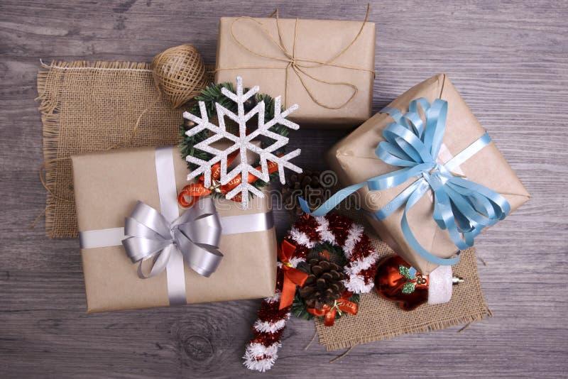 Cadeau de cadeaux de Noël rouge et rustique décoré étendu sur le fond en bois de table images stock