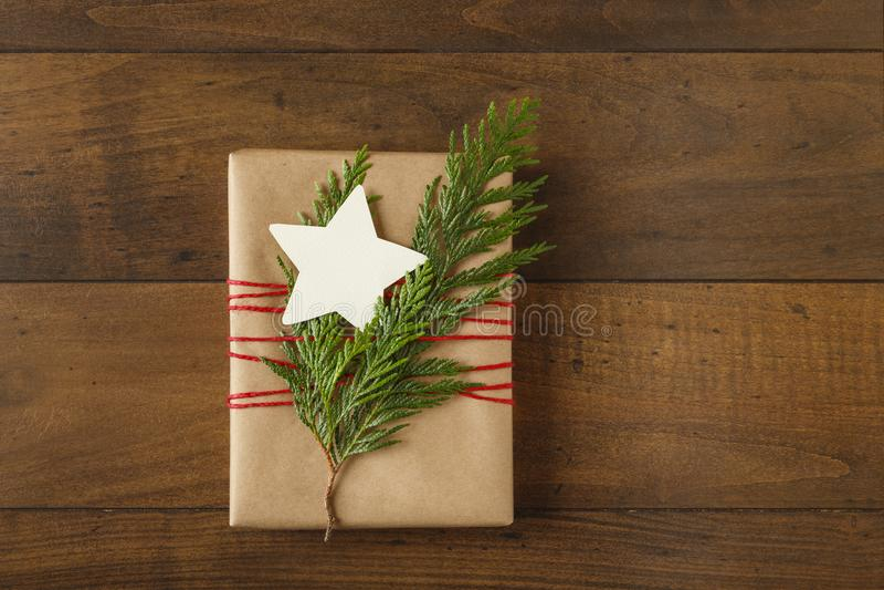Cadeau de Noël actuel avec le papier d'emballage réutilisé et les décorations à feuilles persistantes naturelles sur le fond en b photo libre de droits