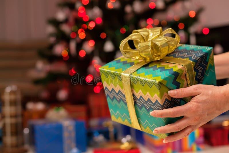 Cadeau de Noël chez la main de la femme - arbre décoré à l'arrière-plan photo libre de droits