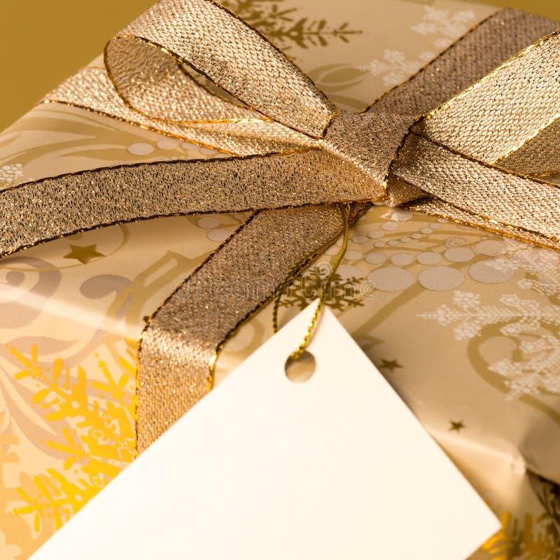 Cadeau de Noël d'or avec l'étiquette vide souhaitant la carte image libre de droits