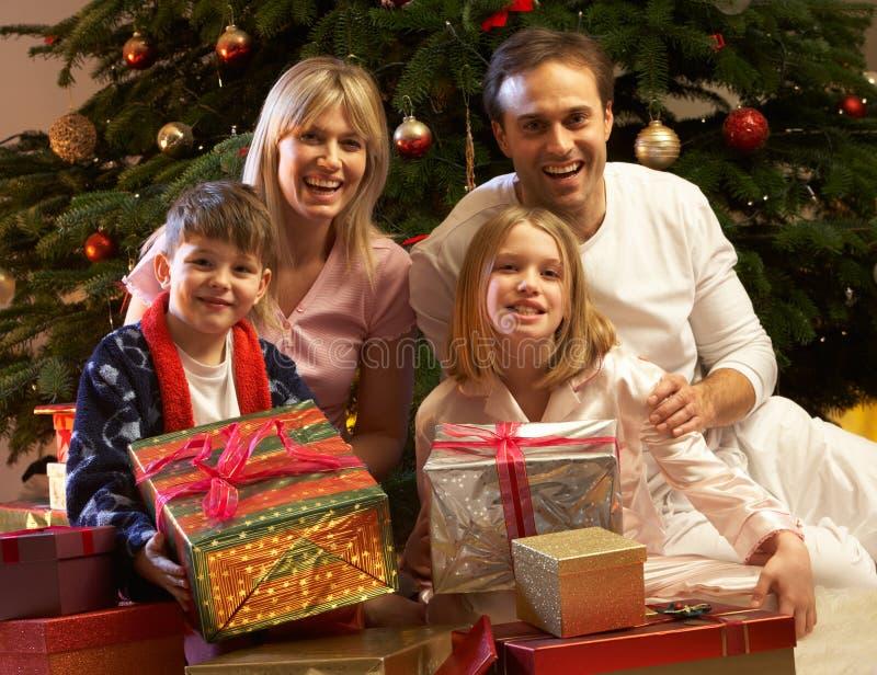 Cadeau de Noël d'ouverture de famille devant l'arbre image libre de droits
