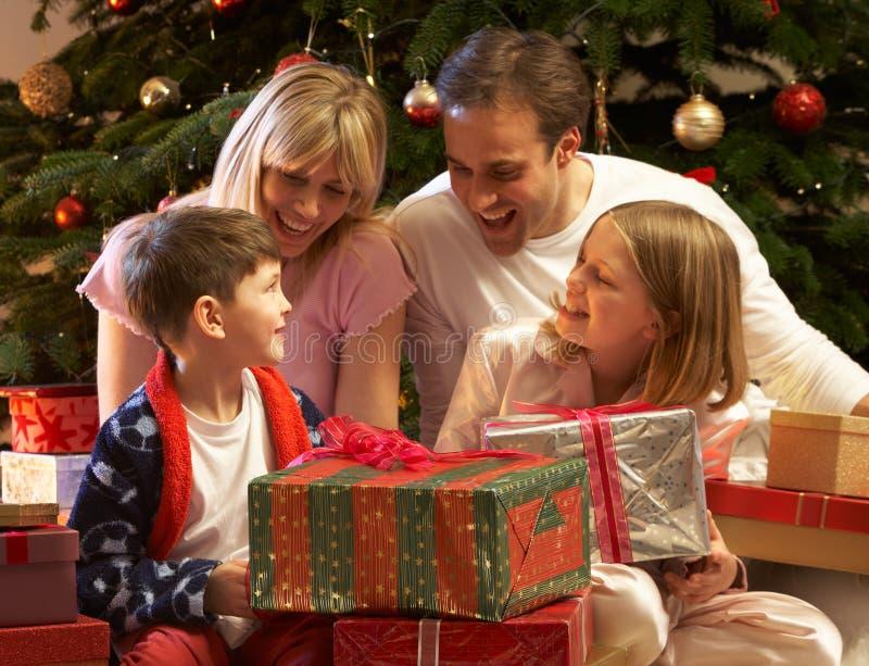 Cadeau de Noël d'ouverture de famille devant l'arbre image stock